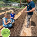 Pinterest pin for how to grow carrots from seed for maximum germination. Photo of a dad and his two daughters planting carrot seeds in the garden.