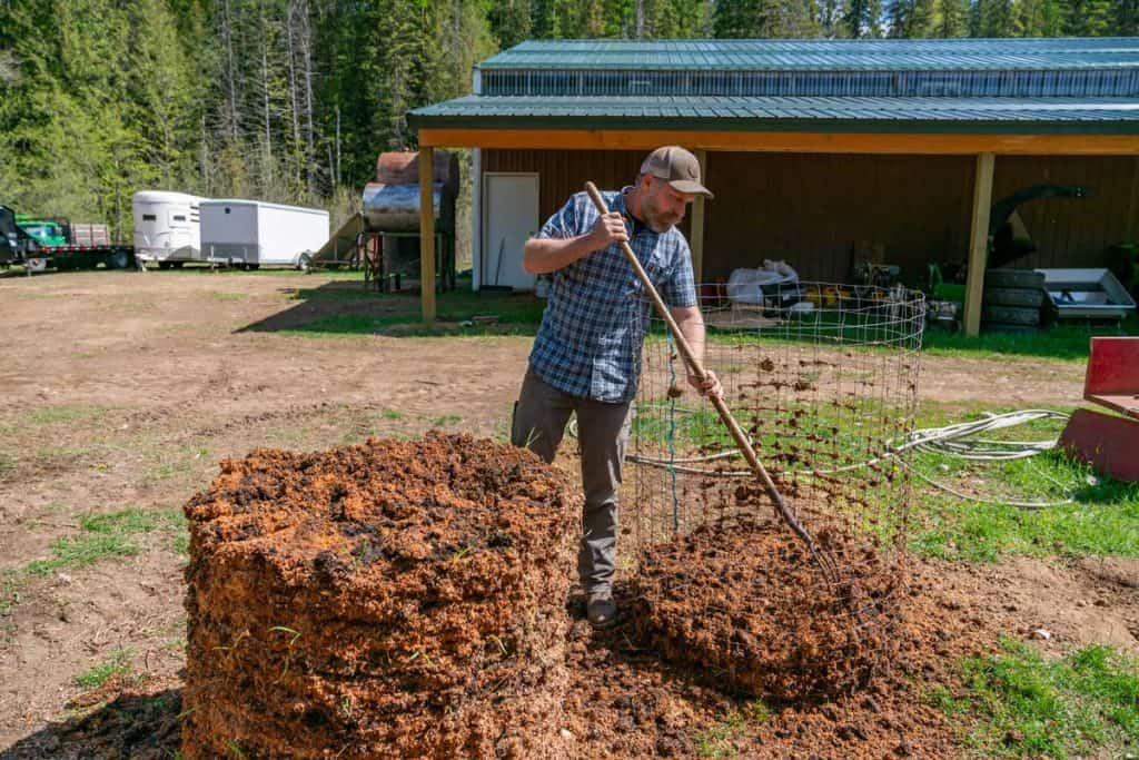 A man turning a compost pile into a wire structure.