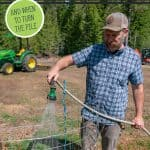 Pinterest pin for compost troubleshooting. Image of a man watering a compost pile.