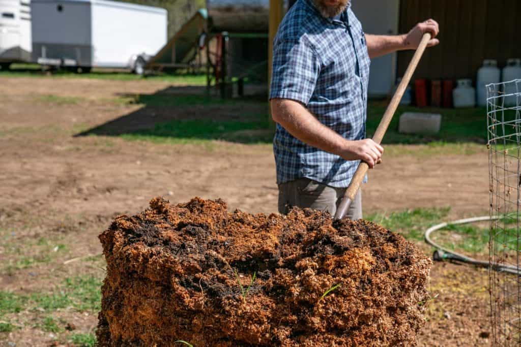 A man scooping compost with a pitchfork.
