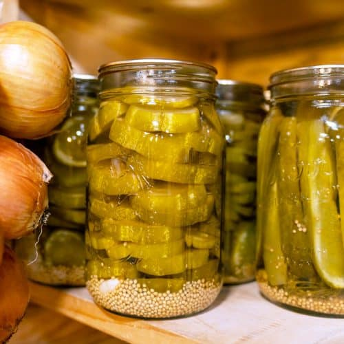Jars of homemade pickles sitting on a pantry shelf.