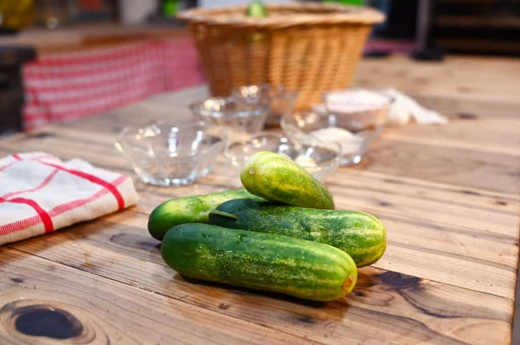 Three cucumbers sitting on a wooden counter with pickle ingredients in glass bowls in the background.