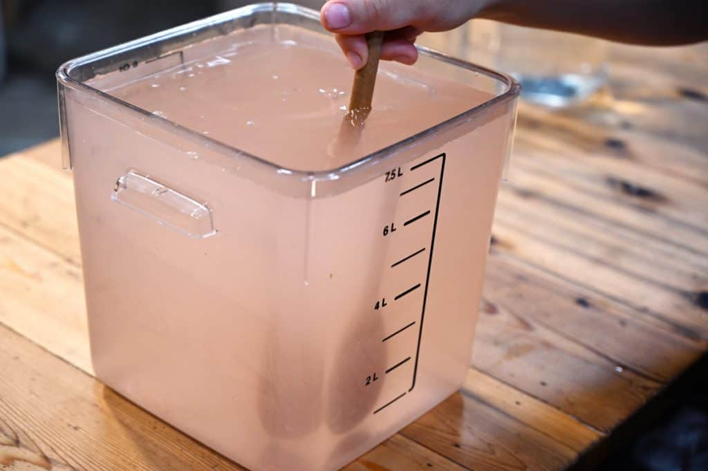 A two-gallon container filled with a saltwater brine and a wooden spoon stirring.
