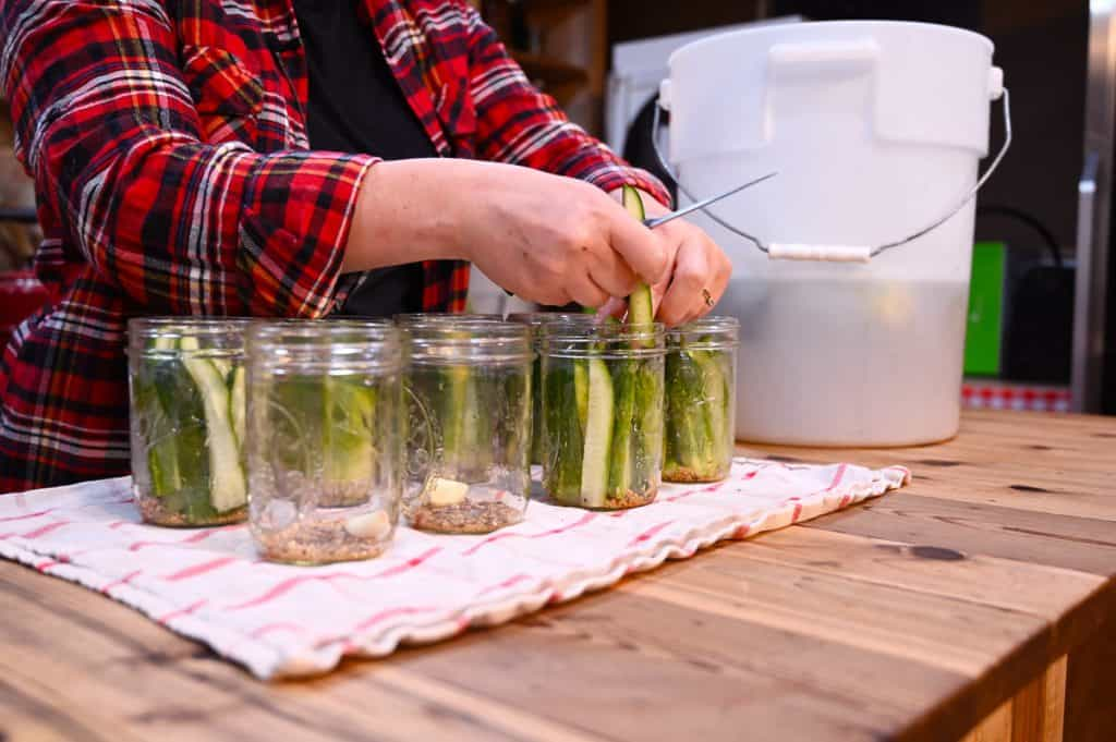 A woman's hands filling canning jars with sliced pickle spears for canning.
