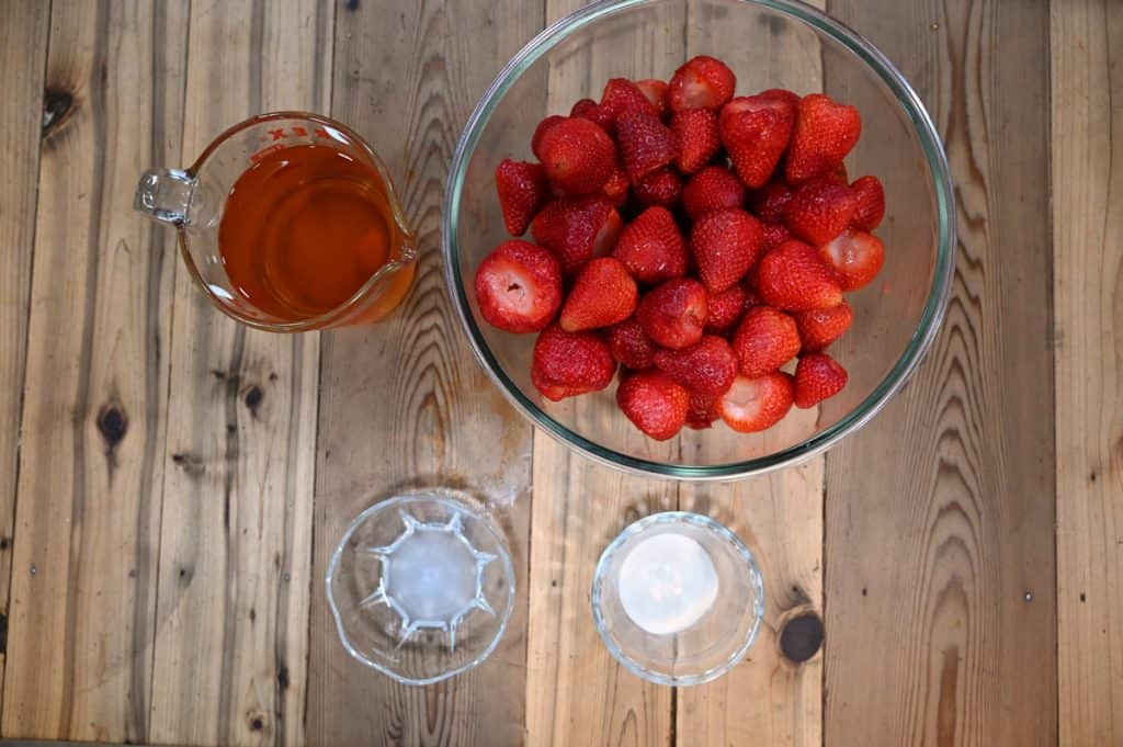 A large glass bowl of strawberries, a measuring cup with white grape juice, and two small bowls with white powder inside.