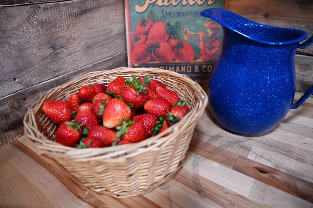 A wicker basket filled with fresh picked strawberries.