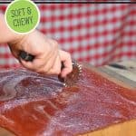 Pinterest pin for homemade fruit leather recipe. Image of a woman's hand cutting strips of fruit leather.