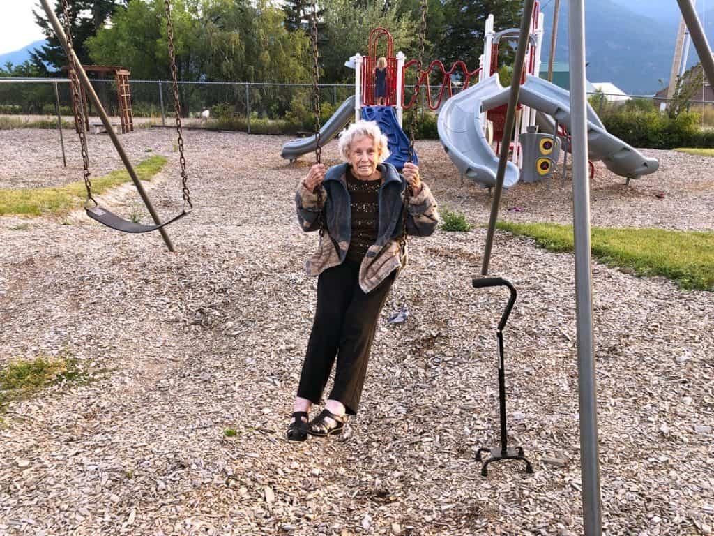 Image of an elderly woman swinging on a swingset.
