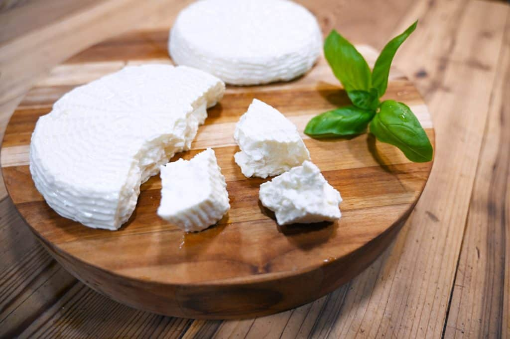 Homemade farmhouse cheese sitting on a cutting board.