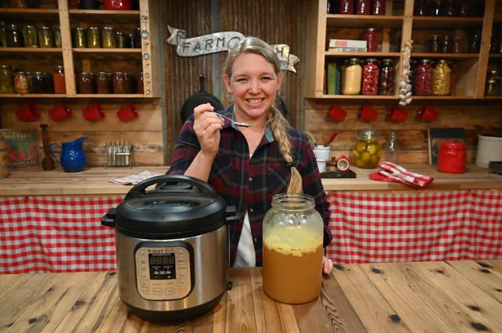 A woman holding a spoon of gelled broth with a gallon of broth and an instant pot on the counter in front of her.
