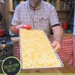 Pinterest pin for how to freeze dry corn. Image of a man holding up a tray of freeze dried corn.