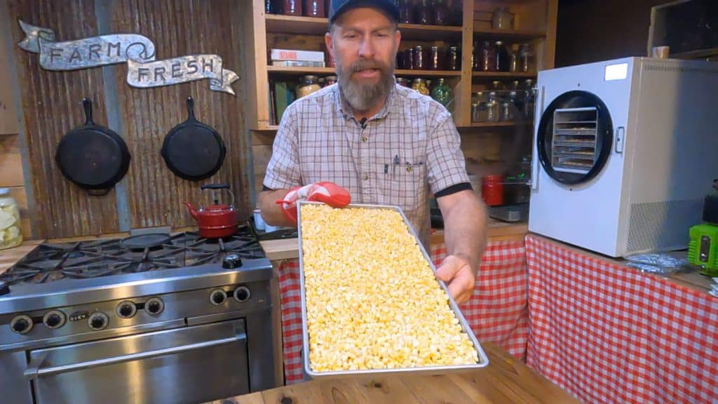 A man holding up a tray of freeze-dried corn.