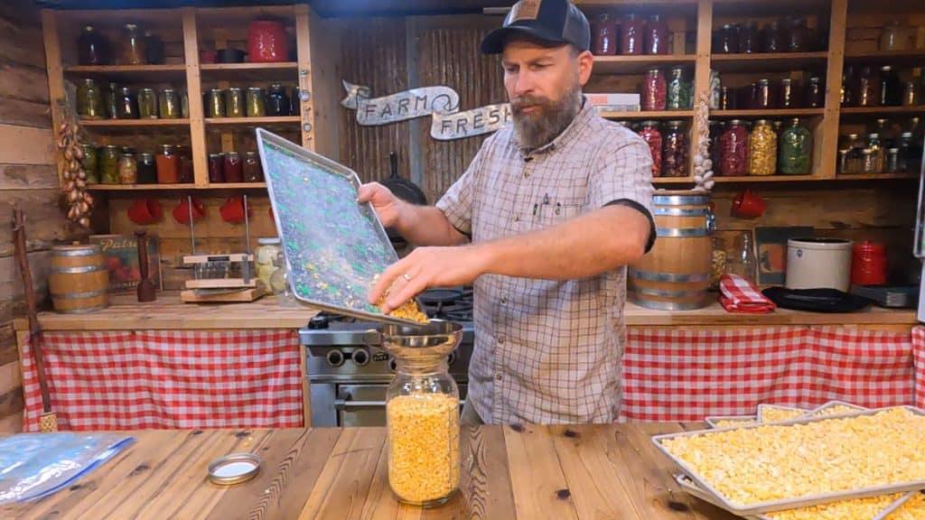 A man pouring freeze dried corn into a half gallon Mason jar.