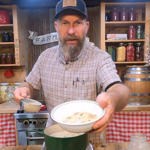 A man holding up a bowl of cream corn.